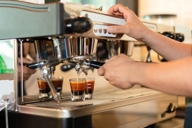 Barista die koffie voorbereiden espresso van machine het brouwen koffie wordt geschoten die.