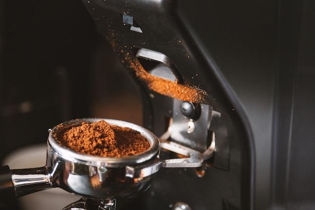 Barista die koffiebonen maalt die koffiemachine met behulp van
