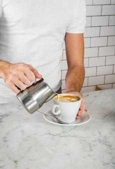 Barista die latte kunst in cappuccino maakt