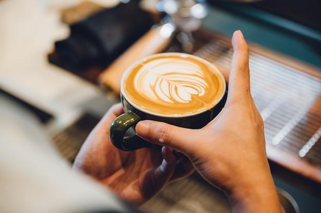 Barista die latte kunst, schotnadruk in kop van melk en koffie maakt