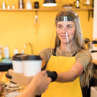 Barista draagt gezichtsbescherming