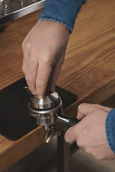 Barista gebruikt een stamper om gemalen koffie in een filterhouder in café op dikke houten tafel te persen professioneel koffiezetten