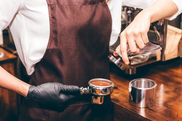Barista gebruikt tamper om koffie in koffiebar te maken