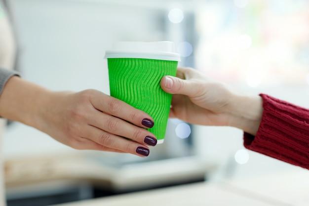 Barista geeft warme koffie in een groene afhaal-papieren beker aan de klant. koffie halen bij caféwinkel