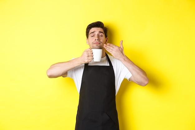 Barista geniet van de geur van koffie in mok, blij met gesloten ogen, gekleed in een zwart schort.
