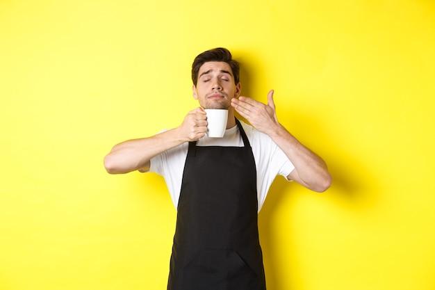 Barista geniet van de geur van koffie in mok, blij met gesloten ogen, gekleed in een zwart schort