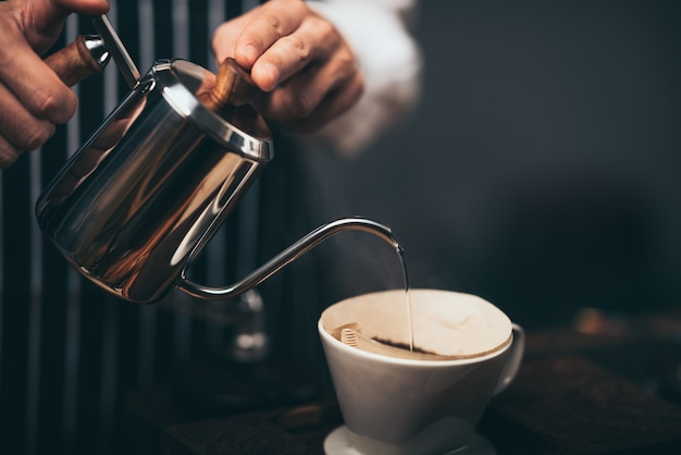 Barista giet heet water uit de ketel over het koffiepoeder om de vers gezette koffie in het koffiecafé te extraheren.