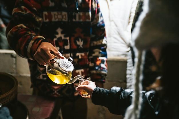 Barista giet hete kamille thee uit theepot naar drinkglas voor tester.