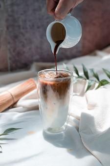 Barista giet melk in een glas ijskoffie