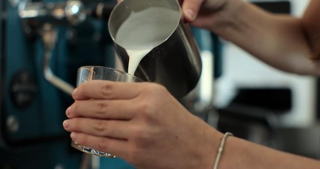 Barista giet melk voor cappuccino. barista schenkt melk over een koffie - latte art maken voor cappuccino.