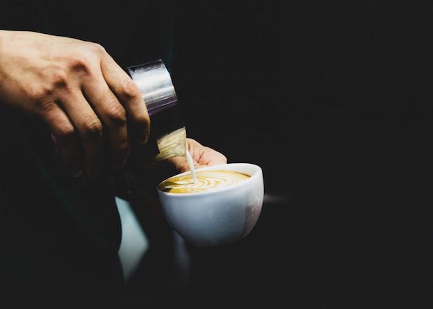 Barista gieten melk in om koffie