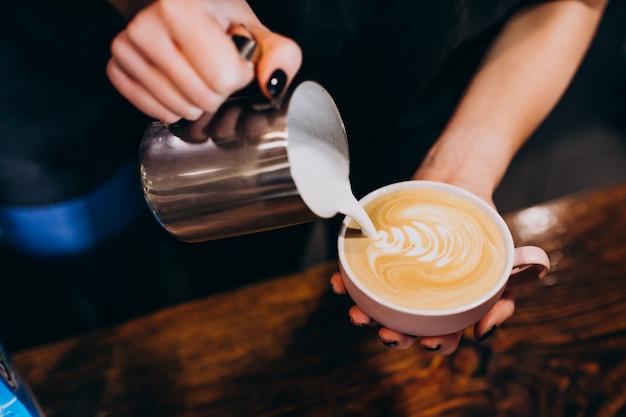 Barista gietende melk in koffie in een koffiewinkel