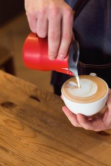 Barista gietende melk in koffiekop voor maak latte art.
