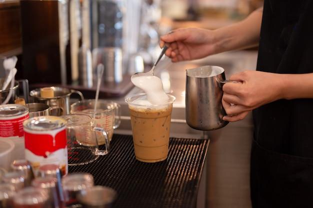Barista hand gegarneerd slagroom bovenop ijskoffie.