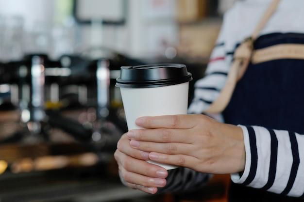 Barista heeft een koffiekopje om mee te nemen.