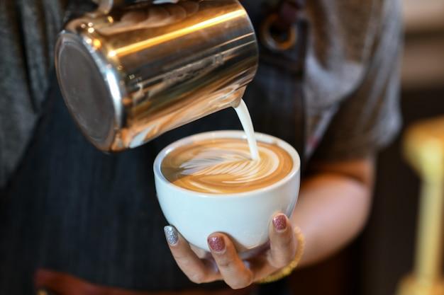 Barista heeft koffie latte bladvormig gemaakt.