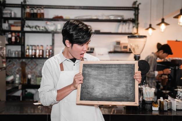 Barista houdt en kijkt een schoolbord op stand voor pub
