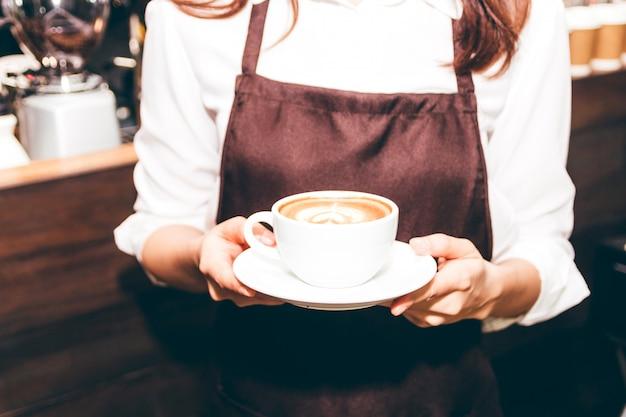 Barista houdt koffie latte kunst in de coffeeshop