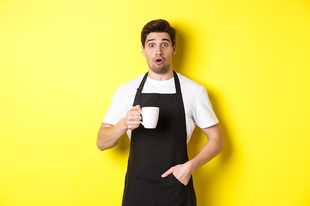 Barista houdt koffiemok vast en kijkt verbaasd, staande in zwart schort café uniform tegen gele achtergrond.