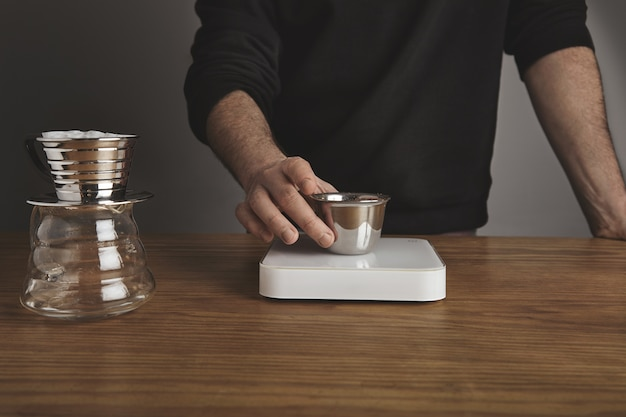 Barista houdt roestvrijstalen beker met gebrande gemalen koffie boven eenvoudige witte gewichten. filterkoffiezetapparaat voor gefilterde koffie dichtbij.
