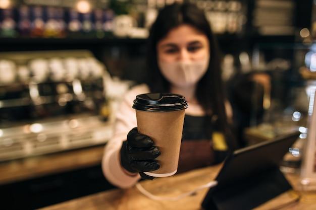 Barista in beschermend gezichtsmasker en zwarte handschoenen geeft kopje koffie in café