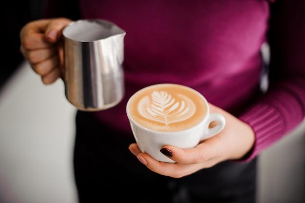 Barista in paars shirt met een koffiekopje met latte art