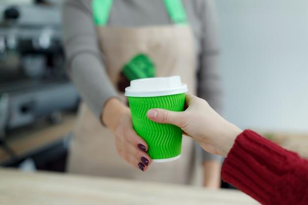 Barista in schort geeft warme koffie in groene afhaalmaaltijden papieren beker aan klant.
