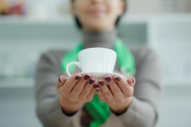 Barista in schort in koffiehuis geeft net gebrouwen verse koffie aan klant
