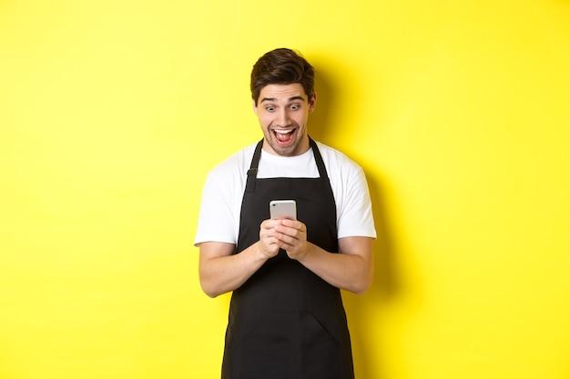 Barista kijkt verrast als het lezen van bericht op mobiele telefoon, staande in zwart schort tegen gele achtergrond.
