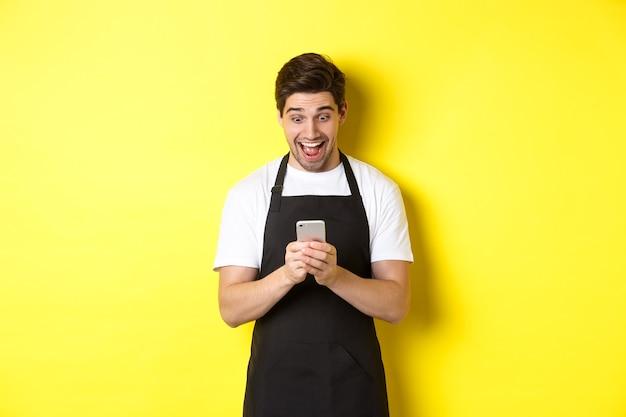 Barista kijkt verrast als het lezen van bericht op mobiele telefoon, staande in zwart schort tegen gele muur