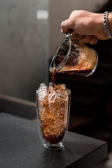 Barista koffie in glas gieten