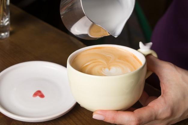 Barista maakt cappuccino met schuimdecoratie