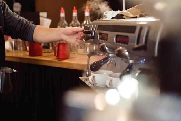 Barista maakt koffie latte kunst met espressomachine in koffie.