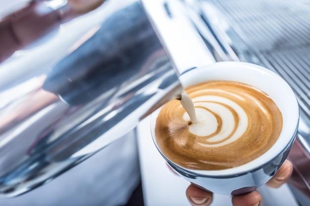 Barista maakt kunstkoffie en giet melk in de beker.