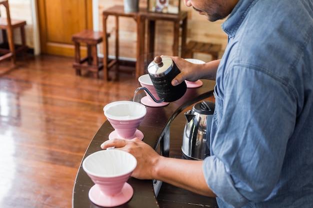 Barista maakt overgietkoffie met een alternatieve methode genaamd dripping. koffiemolen, koffiestandaard en pour-over op een houten teller.