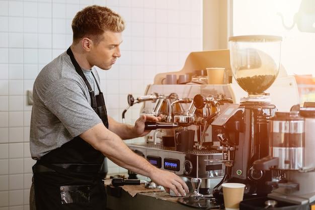 Barista-man die italiaanse espressokoffie maakt met espressomachine in het café