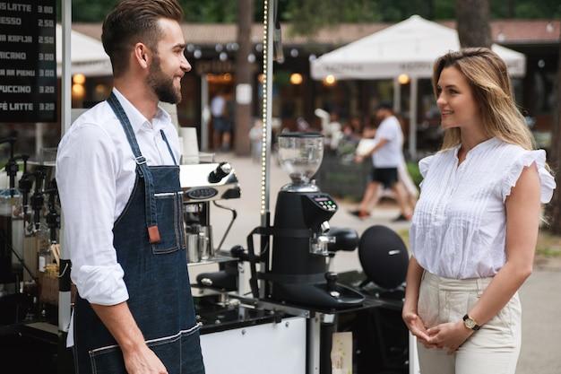 Barista-man en zijn vrouwelijke klant hebben tijdens de zomerdag een klein gesprek naast de verplaatsbare coffeeshop.