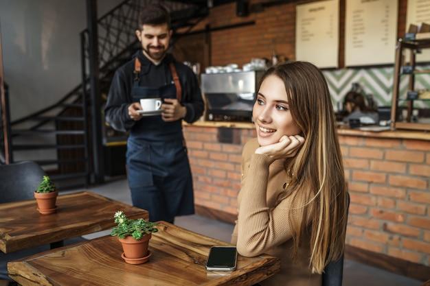Barista man in blauwe schort geven bestelling voor blonde vrouw klant in coffeeshop