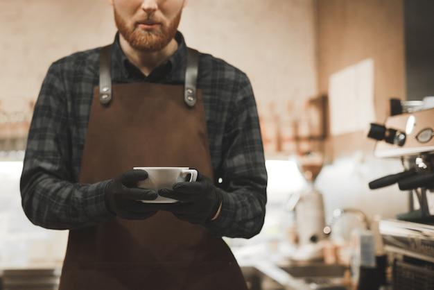 Barista man staat aan het werk in een gezellig café en houdt een kopje geurige koffie.