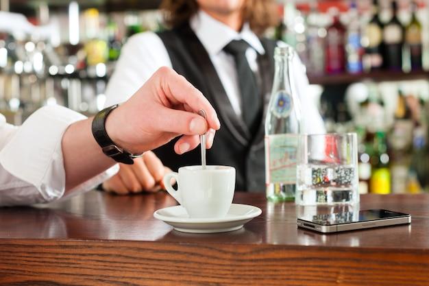 Barista met cliënt in zijn café of coffeeshop