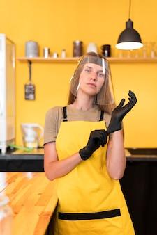 Barista met gezichtsbescherming en handschoenen