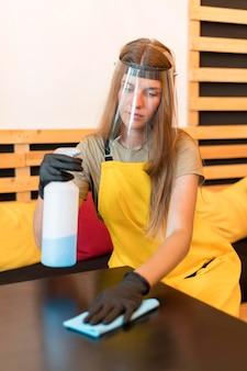 Barista met gezichtsbescherming en handschoenenreiniging