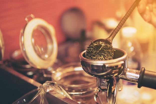 Barista neemt droge groene theeblaadjes om in de machine te zetten voor het maken van thee