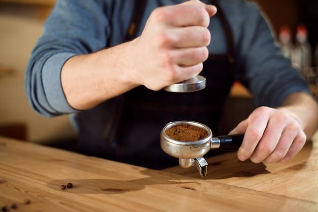 Barista perst gemalen koffie in een koffiewinkel met stamper
