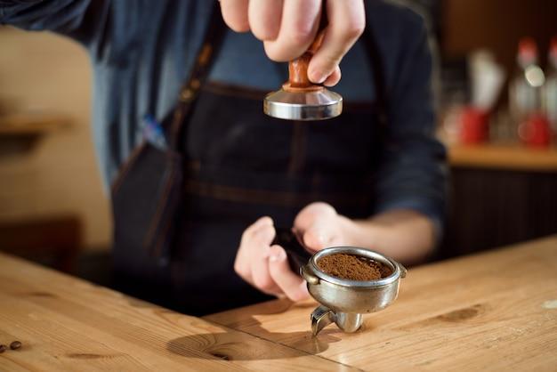 Barista perst gemalen koffie met stamper in een koffieshop.