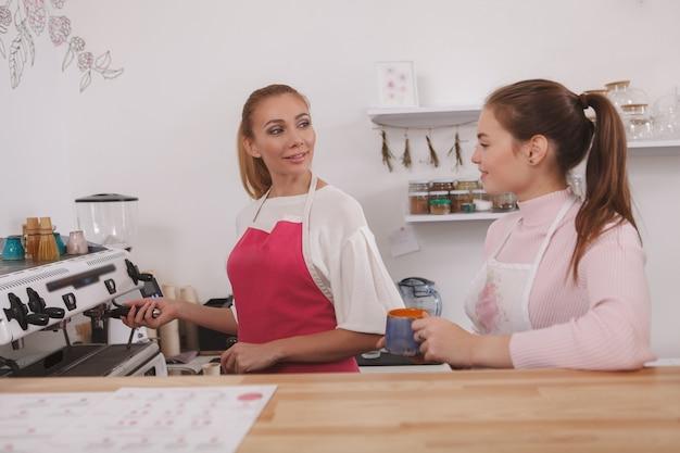 Barista praat met haar collega tijdens het bereiden van koffie op een koffiezetapparaat in het café
