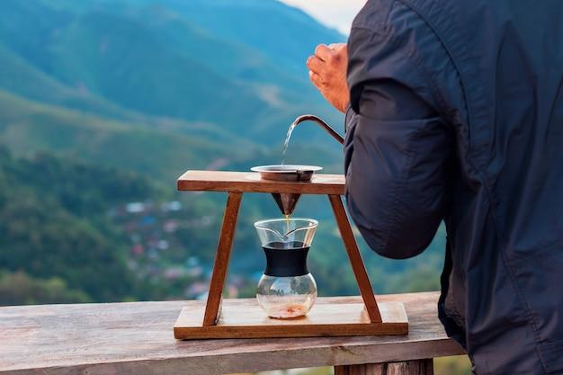 Barista's hand gieten heet water uit pot naar arabica koffie in filter op de top van de berg