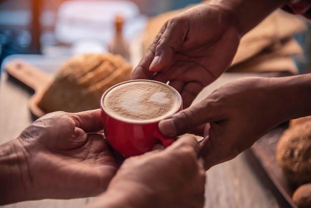 Barista's handen bezorgen koffie aan klanten.