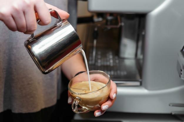 Barista schenkt melk en maakt cappuccino of latte. tekenen op pen.