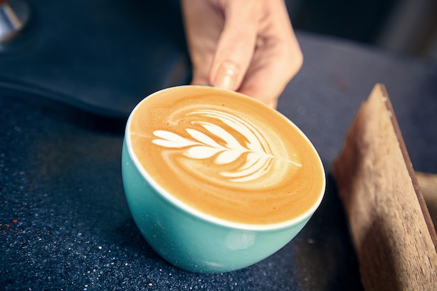 Barista serveert koffie in het koffiehuis. vrouw latte of cappuchino geven aan klant achter de toonbank. restaurant coffee shop concept. getinte foto. kopieer ruimte. vers gemaakte koffie